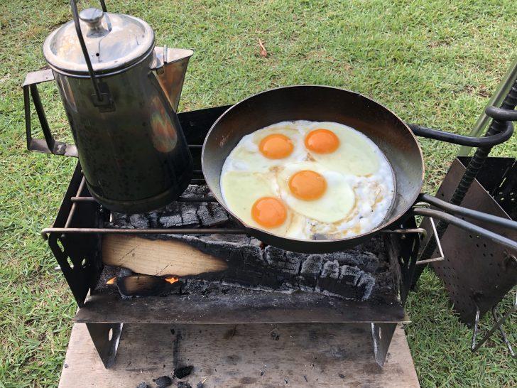 薪グリルで目玉焼きを焼きながらスープ用のお湯を沸かす