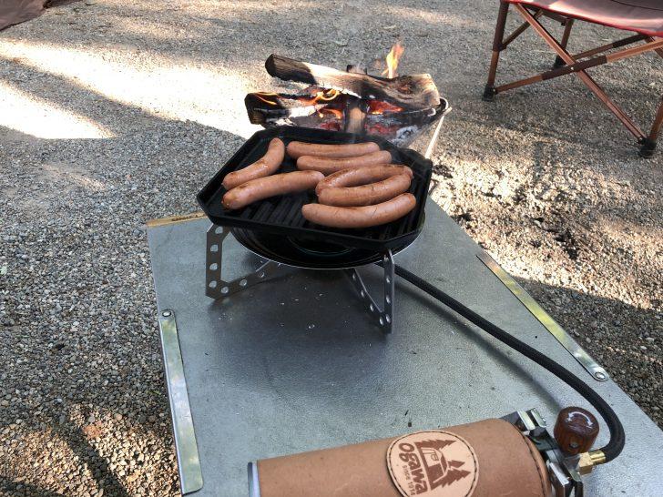 焚き火しながら朝食用のソーセージをユニ鉄で焼く